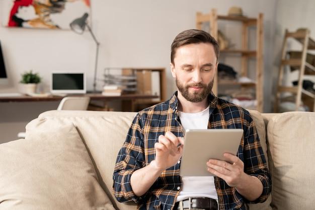 Jeune homme sérieux avec gadget mobile se concentrant sur le réseau tout en regardant son écran et défilement