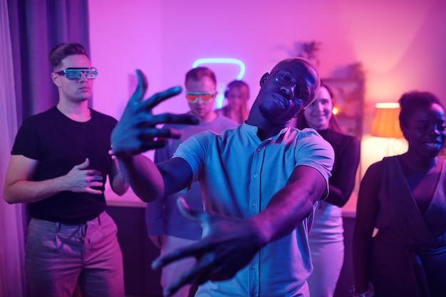 Jeune homme sérieux d'origine africaine en tenue décontractée et lunettes vous regardant tout en se tenant devant ses amis à la fête à la maison