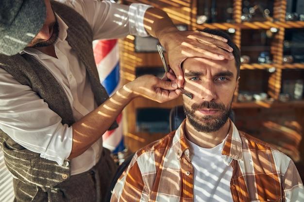 Un jeune homme sérieux se fait raser avec un rasoir droit par un barbier professionnel