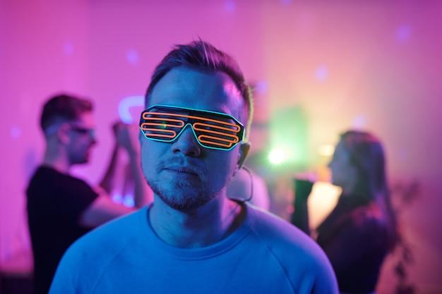 Jeune homme sérieux en tenue décontractée et lunettes disco vous regarde en se tenant debout devant ses amis dansant ensemble à la fête à la maison