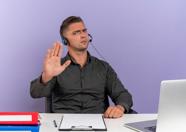 Jeune homme sérieux travailleur de bureau blonde sur les écouteurs est assis au bureau avec des outils de bureau à l'aide de gestes d'ordinateur portable stop main signe isolé sur fond violet avec espace de copie