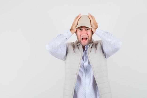 Jeune homme serrant la tête avec les mains tout en criant en chemise, veste sans manches, casquette et à la vue alarmée, de face.