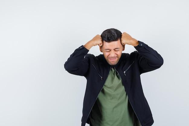 Jeune homme serrant la tête avec les poings en t-shirt, veste et l'air bouleversé, vue de face.