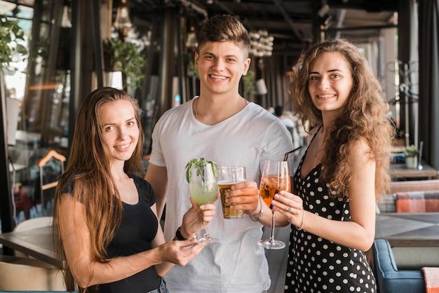 Jeune homme avec ses deux amies tenant des verres de boissons