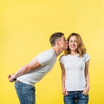 Jeune homme avec ses mains dans le dos, embrassant sa petite amie souriante sur fond jaune