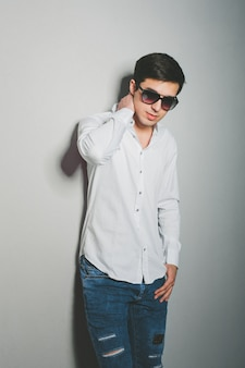 Jeune homme en short et chemise blanche sourit debout près du mur avec des lunettes