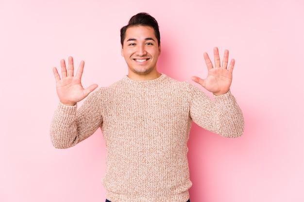 Jeune homme sinueux posant dans un mur rose isolé montrant le numéro dix avec les mains.