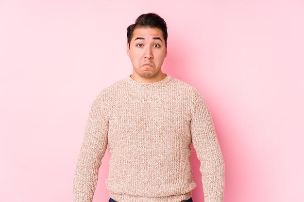 Jeune homme sinueux posant sur rose isolé hausse les épaules et les yeux ouverts confus.