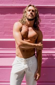 Jeune homme avec six sacs posant sur un mur rose