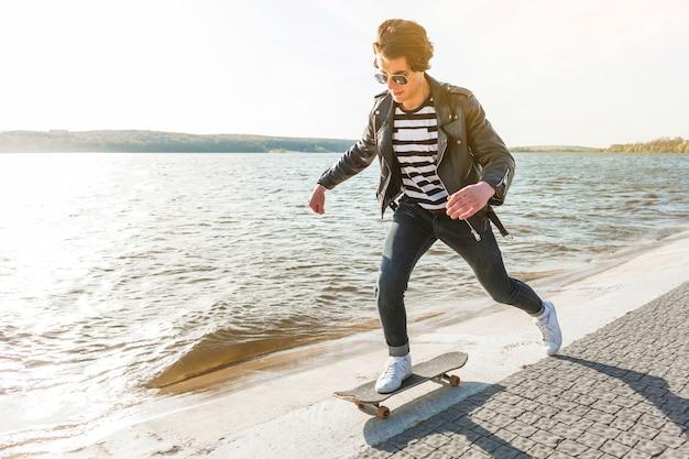 Jeune homme avec un skateboard près de la mer
