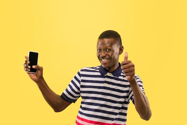 Jeune homme avec smartphone isolé sur mur de studio jaune