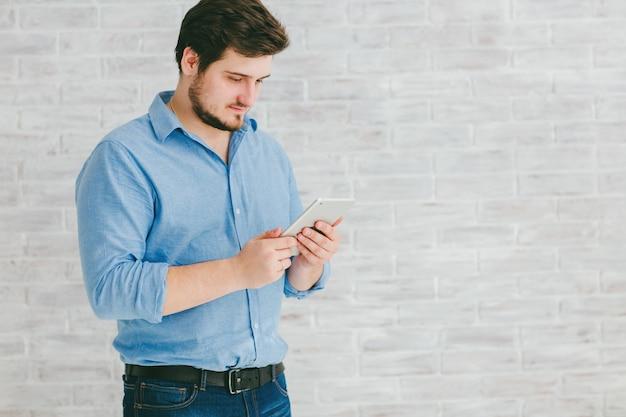 Jeune homme avec smartphone en studio
