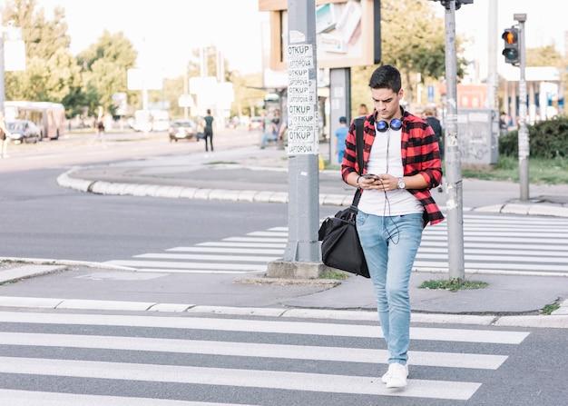 Jeune homme avec smartphone traversant la rue
