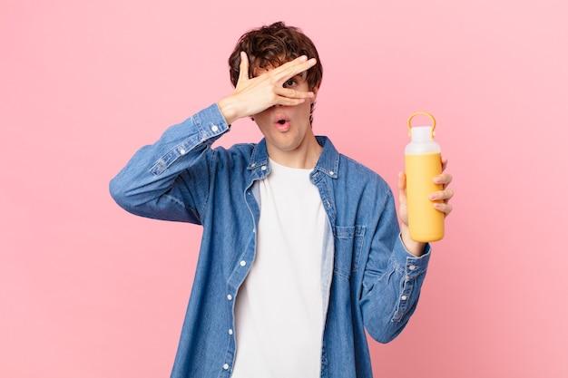 Jeune homme avec un smoothie choqué, effrayé ou terrifié, couvrant le visage avec la main