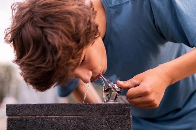 Un jeune homme a soif et boit de l'eau de la fontaine publique de la ville