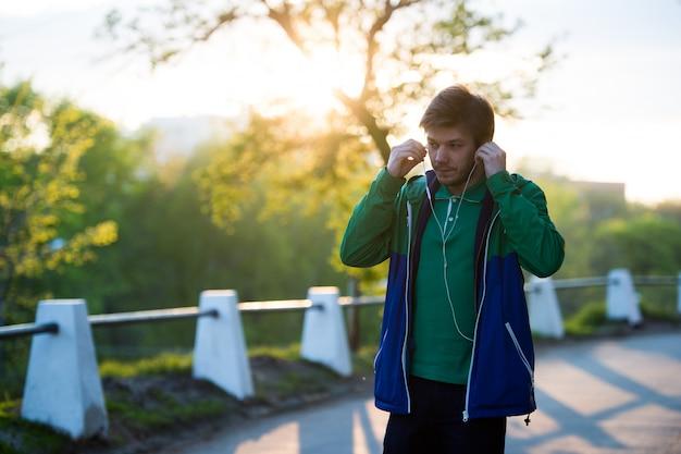 Jeune homme solitaire commun marchant dans la ville en écoutant de la musique avec des écouteurs intra-auriculaires au coucher du soleil. lumière douce et chaude.