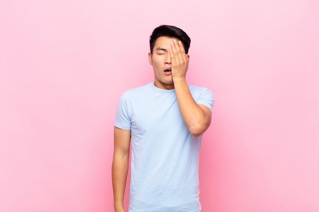 Jeune homme à la somnolence, s'ennuie et bâille, avec un mal de tête et une main couvrant la moitié du visage sur le mur
