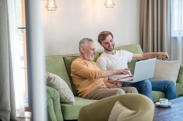 Jeune homme et son père regardant quelque chose en ligne et semblant impliqués