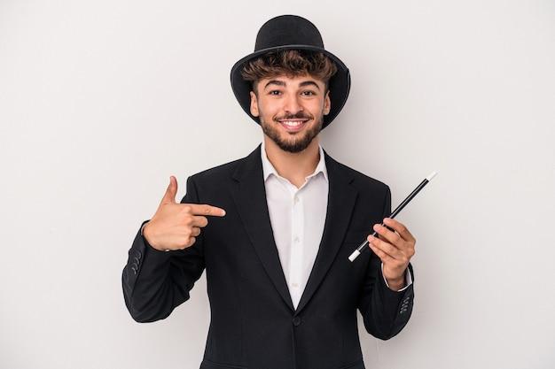 Jeune homme sorcier arabe tenant une baguette isolée sur fond blanc personne pointant à la main vers un espace de copie de chemise, fier et confiant