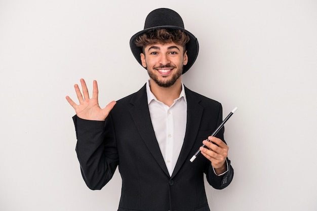 Jeune homme sorcier arabe tenant une baguette isolée sur fond blanc souriant joyeux montrant le numéro cinq avec les doigts.