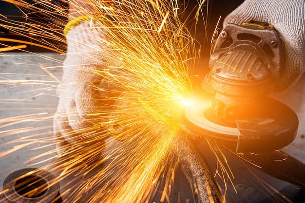 Un jeune homme soudeur dans une meuleuse à gants bleus en métal une meuleuse d'angle dans l'atelier, des étincelles volent sur le côté