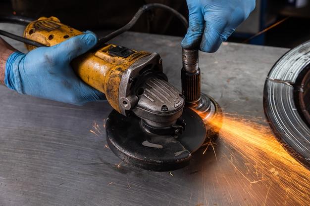 Un jeune homme soudeur dans un moulin à gants bleu métal une meuleuse d'angle dans l'atelier, des étincelles volent sur le côté