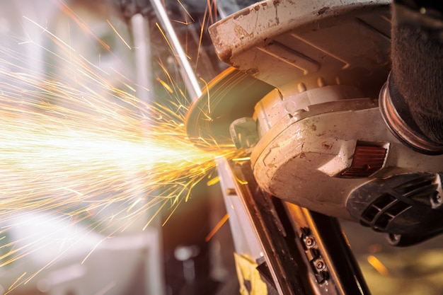 Un jeune homme soudeur meuleuse métal voiture une meuleuse d'angle dans l'atelier, des étincelles volent sur le côté