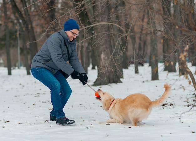 Jeune homme soufflant des flocons de neige de ses mains à son chien golden retriever dans une journée d'hiver. amitié, animal de compagnie et humain.