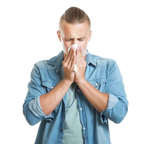 Jeune homme souffrant d'allergie sur fond blanc