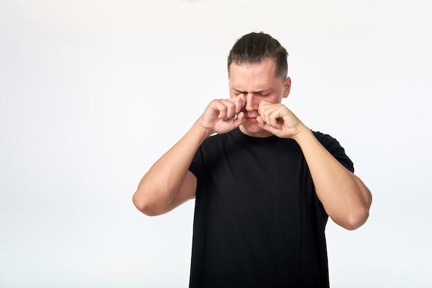 Jeune homme souffrant d'allergie et se gratter les yeux.