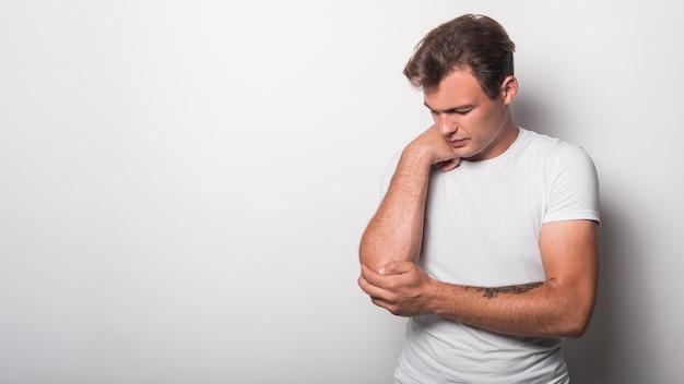 Jeune homme souffrant d'une blessure au coude isolé sur fond blanc