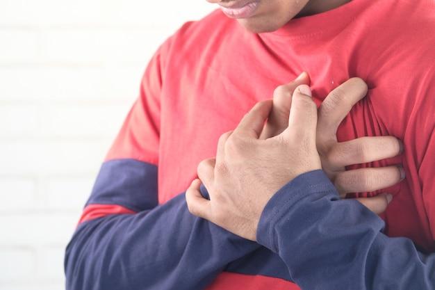 Jeune homme souffrant de douleurs au cœur et tenant la poitrine avec la main.