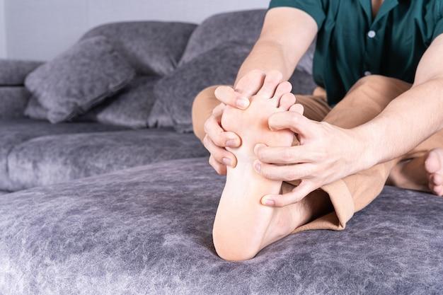 Jeune homme souffrant de douleurs au pied assis sur un canapé à la maison