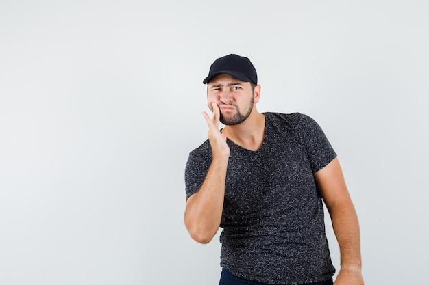 Jeune homme souffrant de maux de dents en t-shirt et casquette, jeans et à la maladie