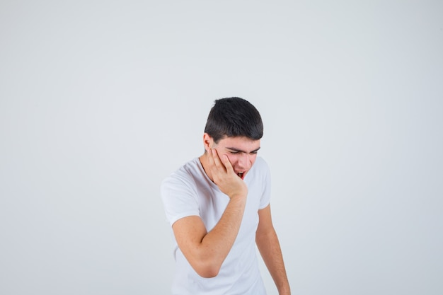 Jeune homme souffrant de maux de dents en t-shirt et à la vue douloureuse, de face.