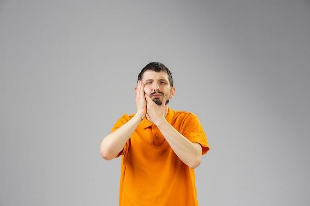 Le jeune homme souffre de la douleur se sent malade et la faiblesse isolted sur le mur