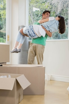 Jeune homme soulevant une femme dans ses bras lors du déballage des boîtes en carton dans la nouvelle maison
