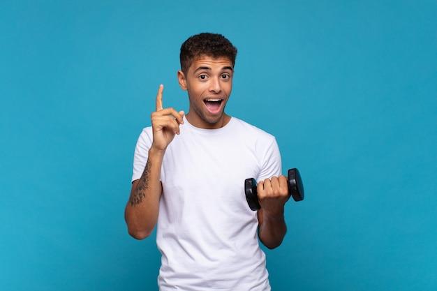 Jeune homme soulevant un haltère se sentant comme un génie heureux et excité après avoir réalisé une idée, levant joyeusement le doigt, eureka!