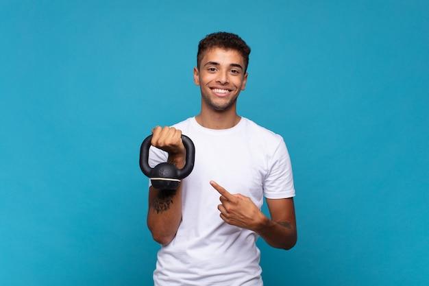 Jeune homme soulevant un haltère souriant joyeusement, se sentant heureux et pointant vers le côté et vers le haut, montrant l'objet dans l'espace de copie