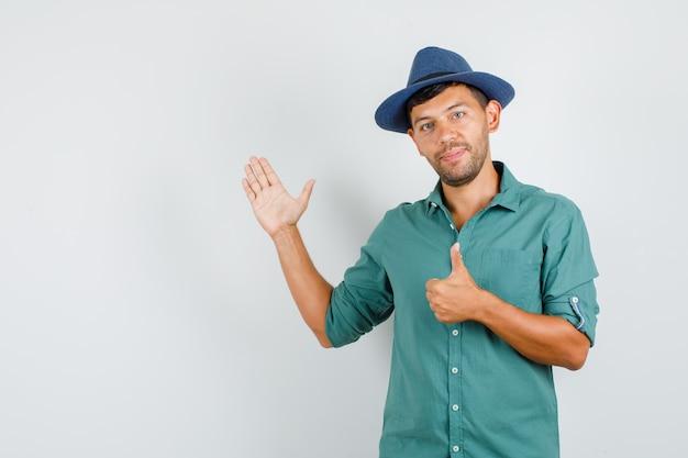 Jeune homme soulevant la paume ouverte avec le pouce vers le haut en chemise
