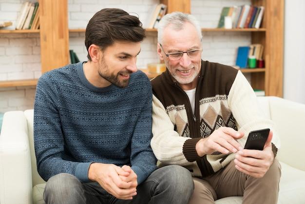 Jeune homme souriant et âgé homme gai à l'aide de téléphone portable sur le canapé