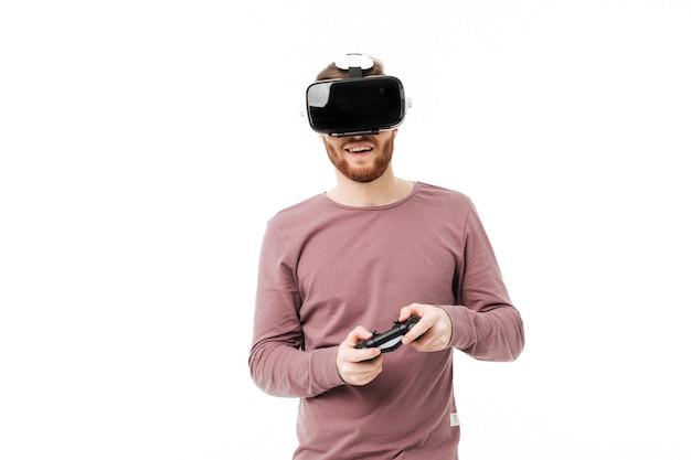 Jeune homme souriant à l'aide de lunettes de réalité virtuelle et jouant au jeu vidéo