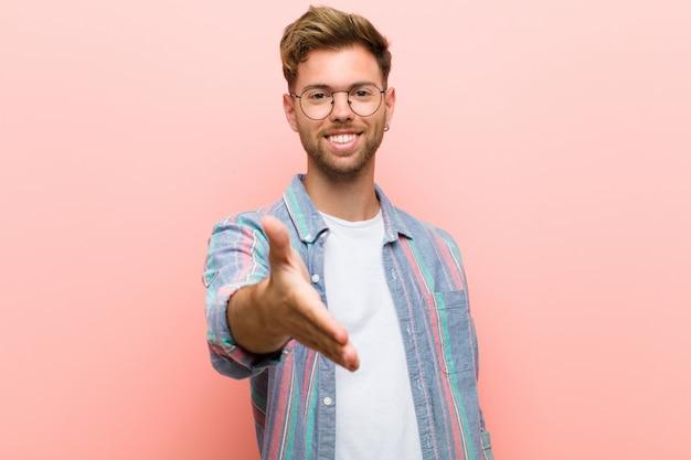 Jeune homme souriant, l'air heureux, confiant et sympathique, offrant une poignée de main pour conclure un accord, coopérant contre le mur rose