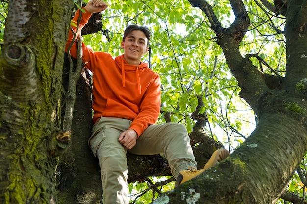 Jeune homme souriant après avoir grimpé sur un arbre. vivre dans la forêt avec un esprit sauvage.