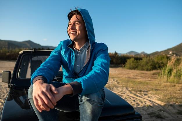 Jeune homme souriant assis sur un véhicule tout-terrain avec pieds nus regardant l'horizon pendant le coucher du soleil. concept de voyage sur la route.