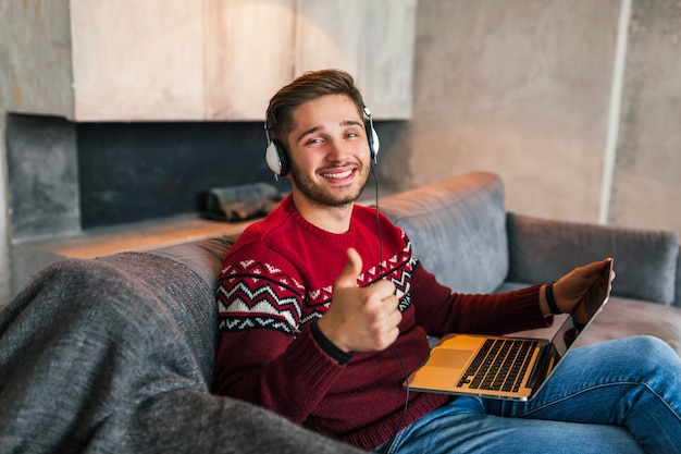 Jeune homme souriant attrayant sur le canapé à la maison en hiver dans les écouteurs, vêtu d'un pull en tricot rouge, travaillant sur ordinateur portable, pigiste, heureux, positif, montrant le pouce vers le haut