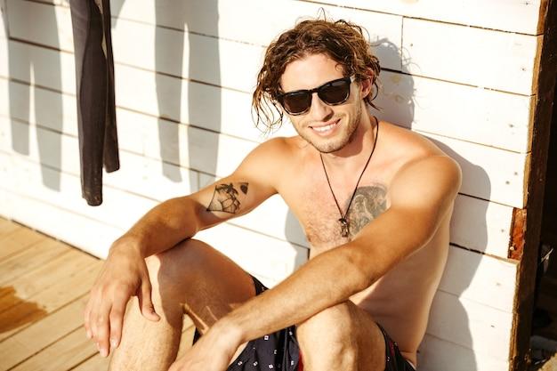Jeune homme souriant au chapeau et lunettes de soleil assis à la cabane de surf