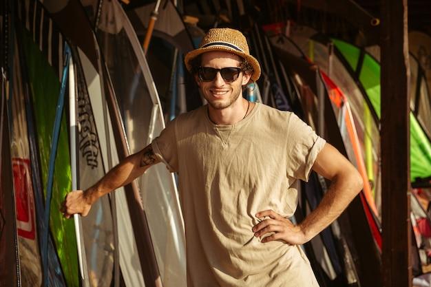 Jeune homme souriant au chapeau et lunettes de soleil debout à la cabane de surf
