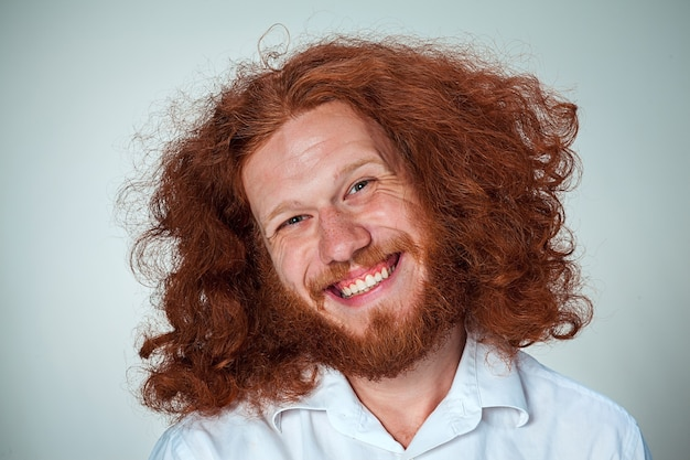 Le jeune homme souriant aux longs cheveux roux regardant la caméra