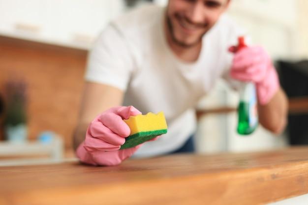 Jeune homme souriant beau nettoyage cuisine moderne.